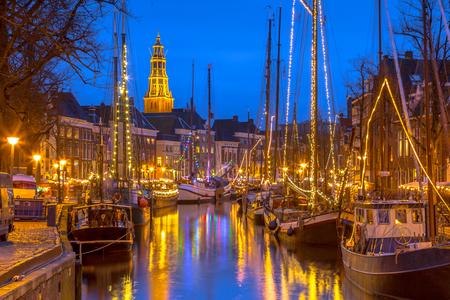 Historische zeilschepen afgemeerd aan rivierkade op het jaarlijkse Winterwelvaart-festival rond Kerstmis. De oude tijden herbeleven in het historische deel van de stad Groningen.