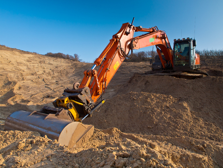 Heavy orange excavator at work in a sandpit seen from the front