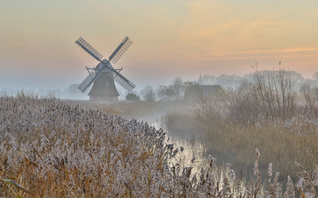Wooden windmill in hazy dutch landscape at sunrise with rime