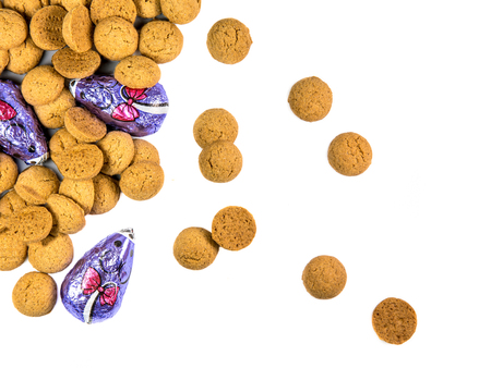 Scattered bunch of Pepernoten cookies and chocolate mice as Sinterklaas decoration on white background for dutch sinterklaasfeest holiday event on december 5th