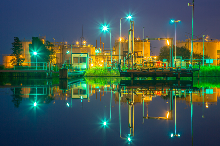 Docking site near water at a small oil refinery in a chemical industrial area in twilight Stock Photo