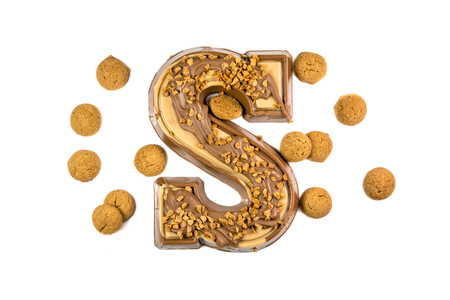 Decorated Chocolate letter with bunch ginger nuts or pepernoten as Sinterklaas decoration on white background for dutch sinterklaasfeest holiday event on december 5th