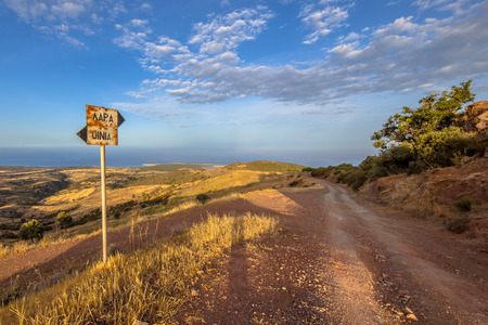 Signposted dirt road with view over sea on Cyprus Island. The Mediterranean landscape has hot semi-arid climate type BSh with corresponding dry subtropical vegetation