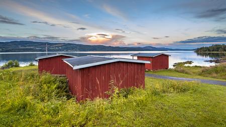 Idyllic red wooden cabins overseeing lake Mjosa near Lillehammer, Norway. Stock Photo