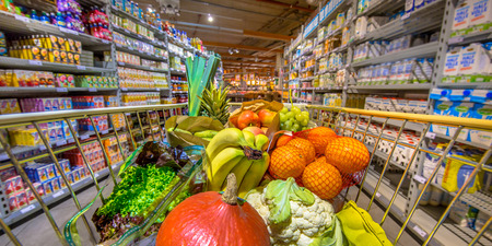 Panorama of Grocery shop cart in supermarket filled up with fresh and healthy food products as seen from the customers point of view Reklamní fotografie - 89779282