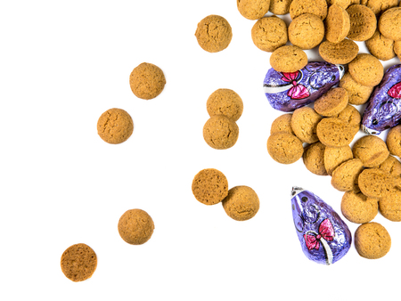Bunch of scattered Pepernoten cookies and chocolate mice as Sinterklaas decoration on white background for dutch sinterklaasfeest holiday event on december 5th