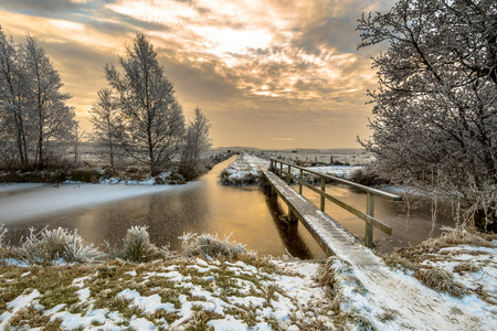 Frozen canal with footbridge in northern part of the province of Drenthe in the Netherlands on a cold morning