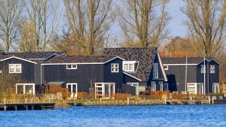 Wooden Holiday resort houses on the waterfront of lake Sneekermeer in Terherne, Friesland Stock Photo