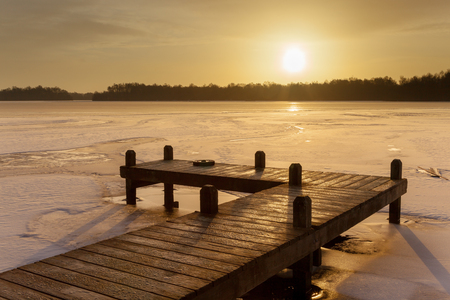Orange Winter Landscape with Lake and jetty covered with ice under amber Colored Sunrise