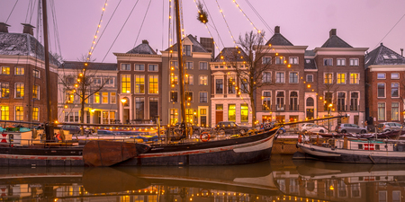 Historic buildings on Hoge der Aa Quay with ships in Groningen city centre at sunset, Netherlands