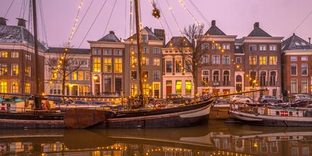 Historische gebouwen op Hoge der Aa Quay met schepen in het stadscentrum van Groningen bij zonsondergang, Nederland Stockfoto