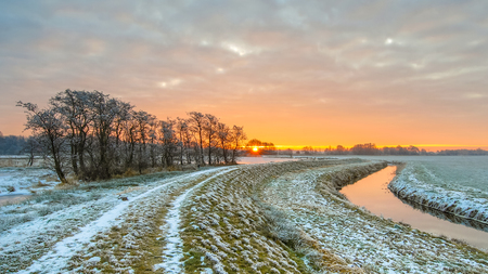 Dike near Meandering River in Frozen grassland landscape on early morning with rising sun under beautiful sky