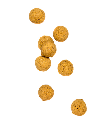 Number of scattered Pepernoten cookies from above as Sinterklaas decoration on white background for dutch sinterklaasfeest holiday event on december 5th