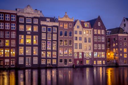 Oude traditionele vintage gekleurde grachtenpanden 's nachts in Amsterdam
