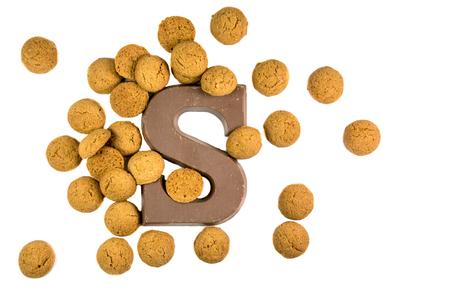 Handvol Pepernoten cookies of gember noten met chocolade letter als Sinterklaas decoratie op een witte achtergrond voor Nederlandse sinterklaasfeest vakantie evenement op 5 december