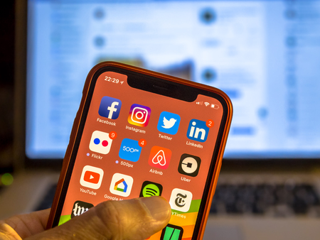 NEW YORK, USA - NOVEMBER 7, 2017: Social media app icons on new smartphone display close-up around other iphone applications with laptop in background Reklamní fotografie - 89899406