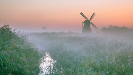 Dutch Polder landscape with Characteristic traditional windmill on a foggy september morning in the Netherlands
