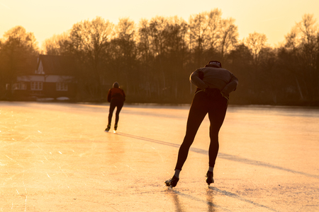 Ice speed skating silhouettes in orange light of setting sun on frozen lake in the Netherlands Stock Photo
