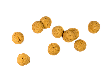 Small amount of scattered Pepernoten cookies or ginger nuts from above as Sinterklaas decoration on white background for dutch sinterklaasfeest holiday event on december 5th