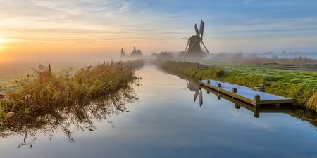 Colorful landscape of Windmill in dutch polder along canal in early morning light during foggy sunrise