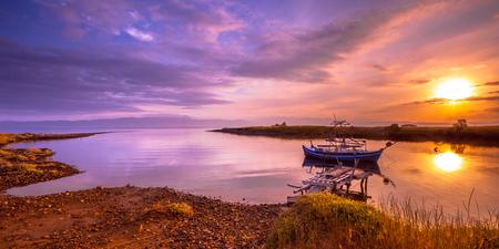 Fishing vessel in river inlet bay under orange sunrise on Lesbos island, Greece