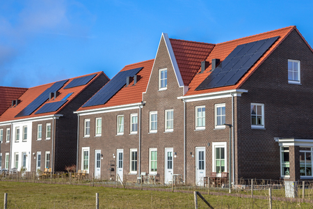 Modern row houses with solar panels, brown bricks and red roof tiles in neoclassical style in Groningen Netherlands on sunny day Stok Fotoğraf