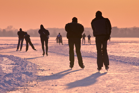 Ice Skaters on frozen lake seen on their back under orange sunset Stock Photo