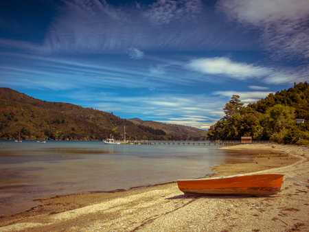 Boat on the Shore of a Fiord in Marlborough Sounds, South Island, New Zealand Stock Photo