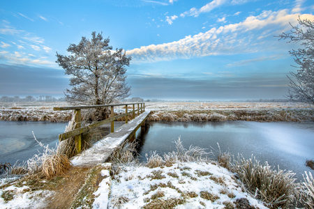 Footbridge over Frozen canal with footbridge in the province of Drenthe in the Netherlands on a cold morning