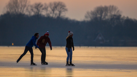 GRONINGEN, THE NETHERLANDS - JANUARY 26, 2017: People are Ice speed skating like silhouettes in orange light of setting sun on frozen lake in the Netherlands