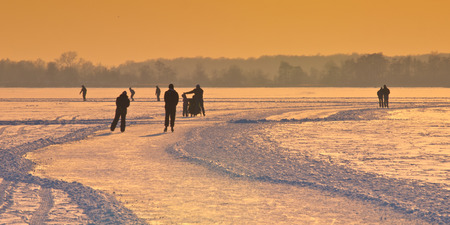 Dutch Ice Skaters on frozen lake seen on their back under orange sunset