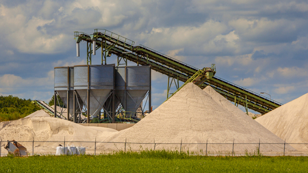 Sand mining terminal with conveyer belts and silos on a summer day
