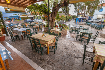 Traditional Restaurant terrace in village around big tree on a greek island in the mediteranean sea