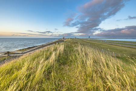 Afsluitdijk dutch dike with fences motorway and cycling track during  sunset with clouded sky Stock Photo