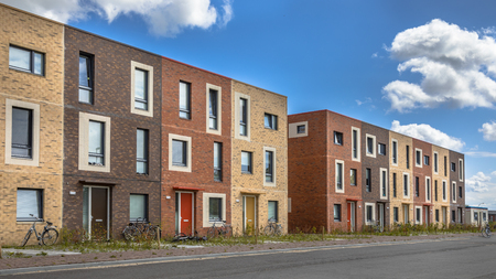 Modern Social housing under blue sky in terra colors containing modest family apartment houses in Ypenburg, The Hague, Netherlands Stock Photo