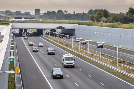 Afternoon traffic on A4 motorway near The Hague Randstad area. Highway crossing aquaduct tunnel with urban area of Rotterdam in backdrop, Netherlands. Stock Photo