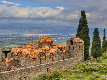 Monastery buildings in the medieval Byzantine ghost town-castle of Mystras, with city of Sparta in background Peloponnese, Greece Editorial