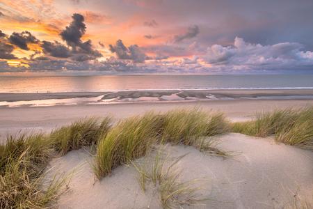 Zonsondergangmening vanaf duinbovenkant over Noordzee en Kanaal in Zeeland, Nederland