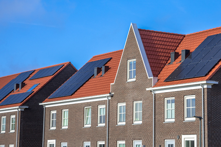 Close up of Modern row houses with solar panels, brown bricks and red roof tiles in neoclassical style in Groningen Netherlands Reklamní fotografie