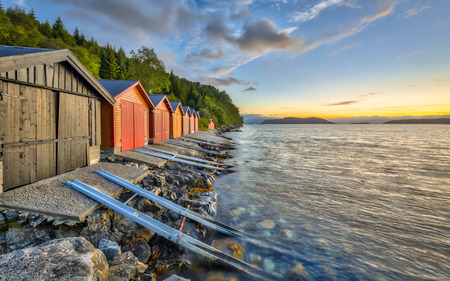 Colorful Boathouses in Norwegian fjord near Rodven in More og Romsdal province Norway at sunset