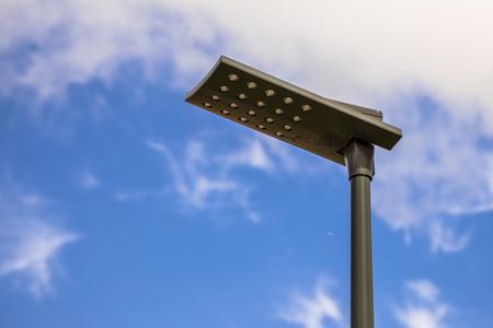 Lampione stradale a LED con palo nero e armatura contro il cielo estivo blu
