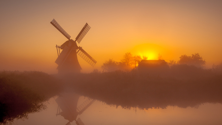 Characteristic historic dutch windmill along a wide canal in a polder wetland on a foggy september morning in the Netherlands