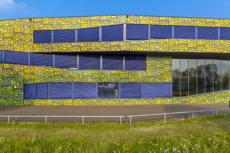 Architecture detail of modern design high school in bright colors and flowers in front