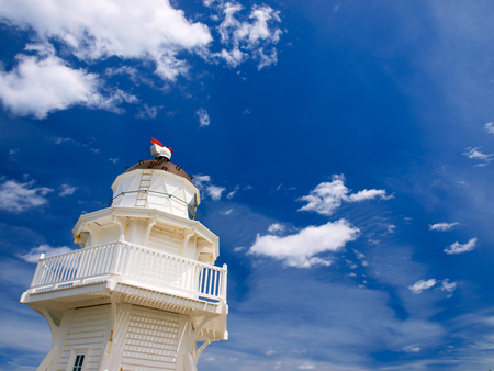 White Wooden lighthouse against blue sunny summer sky with light clouds on Otago coast New Zealand