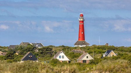 Red lighthouse between houses of village of Schiermonnikoog isand