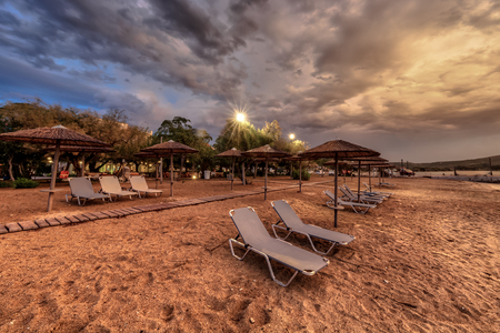 Reed parasols on empty peleponnese beach during cloudy sunset Editorial
