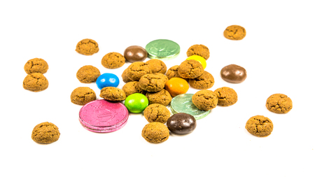 Bunch of pepernoten cookies, sweets and chocolate money frontal view on white background for annual Sinterklaas holiday event in the Netherlands on december 5th Standard-Bild