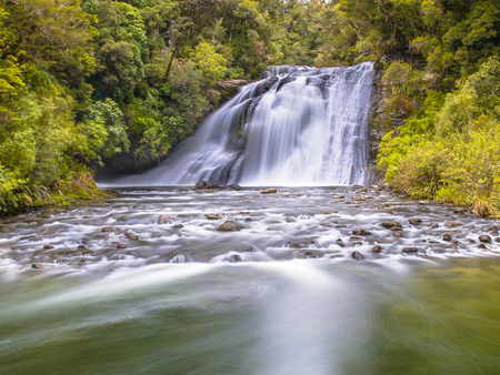 Long exposure image of a waterfall in lush rainforest of Te Urewera National Park in New Zealand