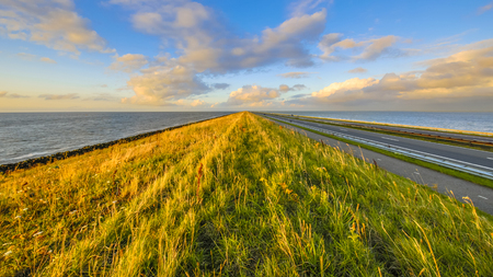 Afsluitdijk dutch dike with motorway and cycling track at sunset with clouded sky Фото со стока - 110751890