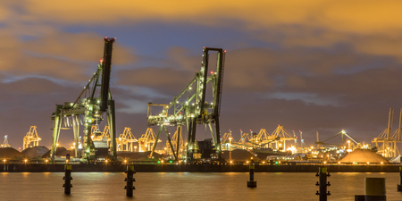 Industrial landscape with Harbor quay and two loading cranes at night in Europoort Maasvlakte Port of Rotterdam Netherlands